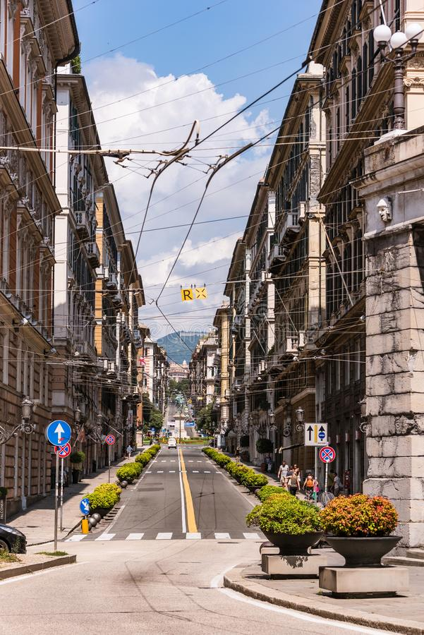 Genoa, Via Roma street with power lines. At the end of that street the town square Piazza Corvetto royalty free stock photos