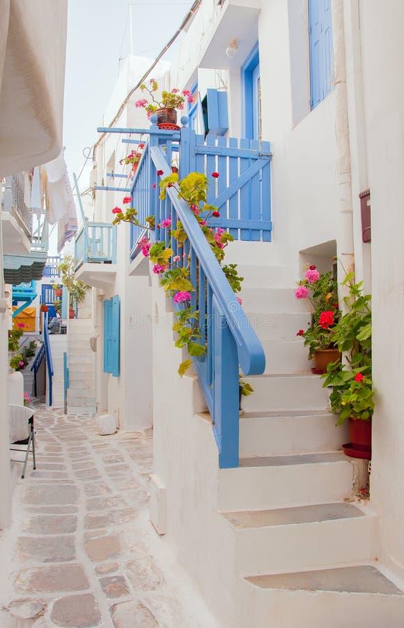 Via romantica dell'isola greca con i fiori immagini stock