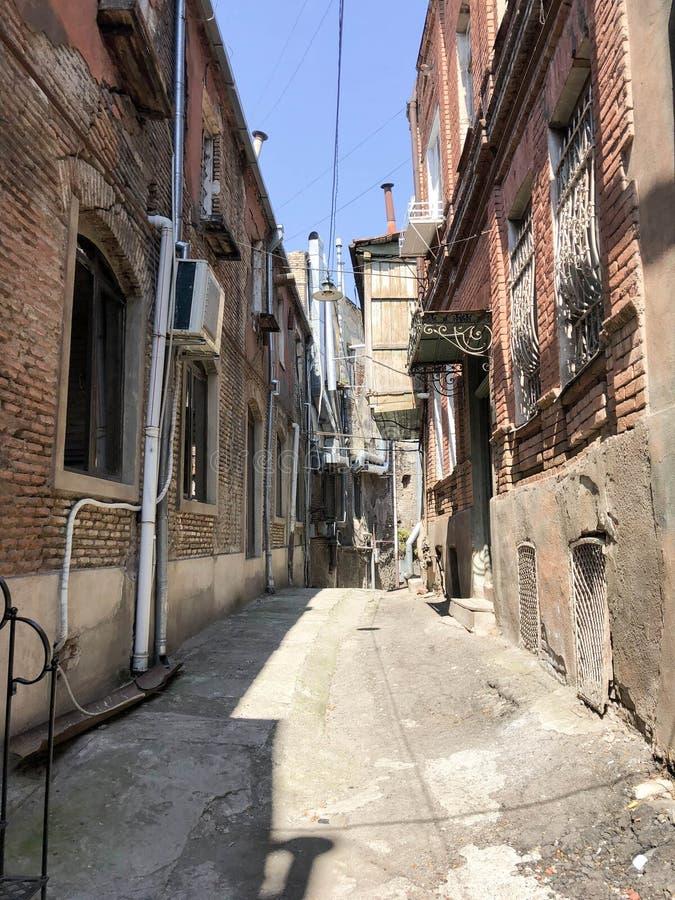 Via stretta, vicolo, tunnel con le vecchie case, costruzioni dai lati in un'area difficile della città, bassifondi Foto verticale fotografia stock