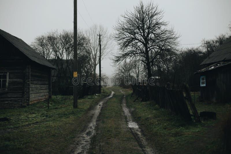 Via in villaggio russo Vecchia casa di legno in primavera Natura sporca intorno immagini stock libere da diritti
