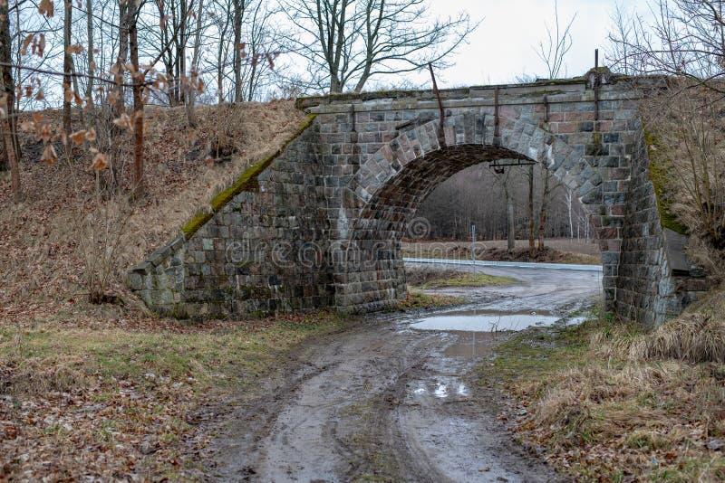 Viadotto di pietra sopra la vecchia strada ferrata Una strada non asfaltata che conduce sotto un vecchio ponte ferroviario fotografie stock libere da diritti