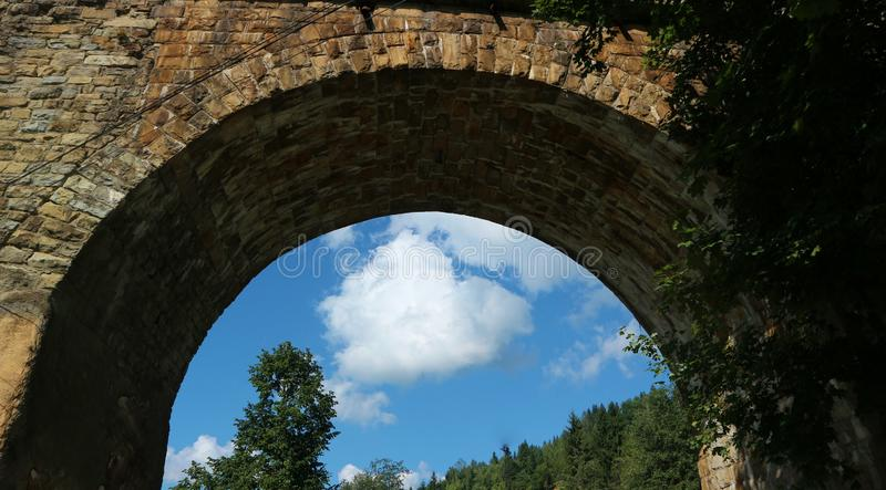 Viaduct brick bridge arch against blue sky. Summer  and dress stock image