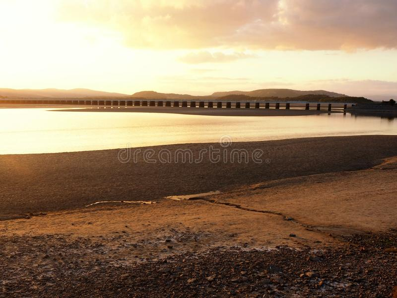 Viaduct over the Kent Estuary, Cumbria, at sunset. Viaduct over the Kent Estuary near Arnside, Cumbria, England, at sunset with a golden sky royalty free stock images