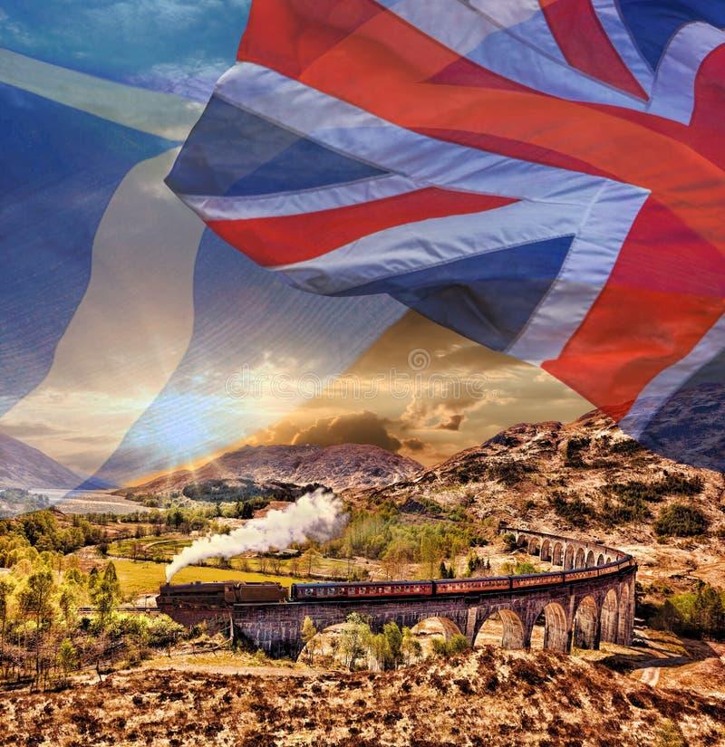 Viaduto Railway de Glenfinnan em Escócia com o trem do vapor de Jacobite contra bandeiras escocesas do ANG ingleses imagem de stock royalty free