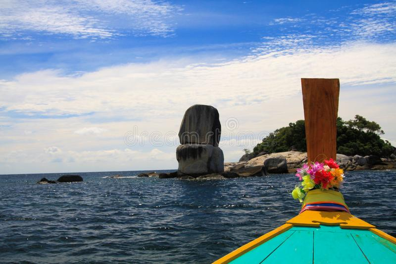 Viagem do barco às rochas empilhadas contra o céu azul com a curva do barco do langtail decorada com flores fotografia de stock royalty free