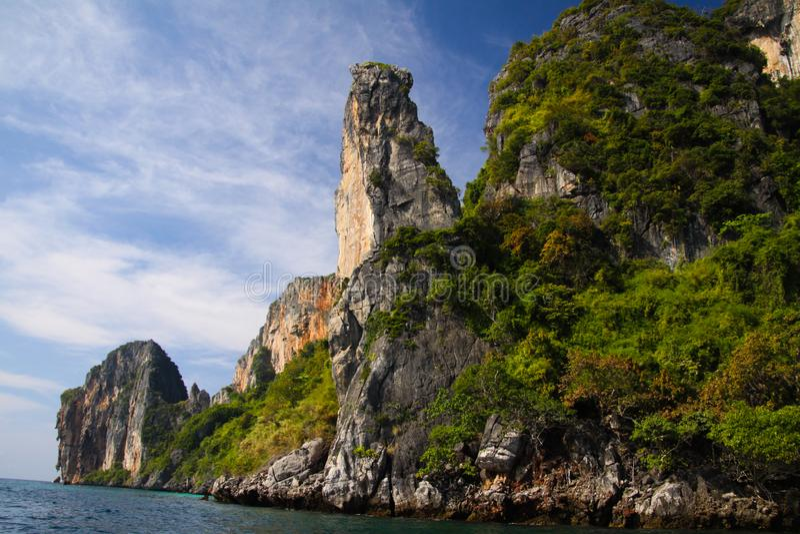 Viagem do barco ao longo da costa a linha da ilha tropical Ko Phi Phi ao longo das formações de rocha impressionantes sob o céu a imagem de stock royalty free