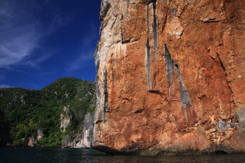 Viagem do barco ao longo da costa a linha da ilha tropical Ko Phi Phi ao longo da parede vermelha íngreme impressionante da rocha imagem de stock