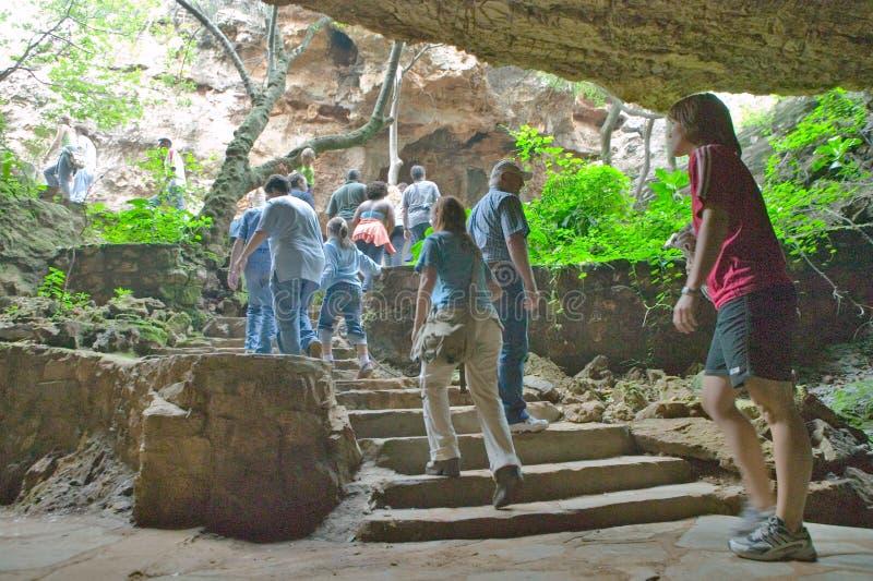 A viagem do homem é simbolizada como os turistas andam fora das cavernas no berço da humanidade, um local do patrimônio mundial e foto de stock