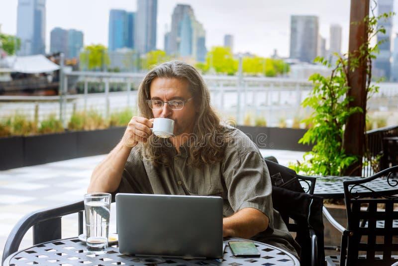 Viagem do homem de negócios, trabalhando na xícara de café da terra arrendada das mãos de New York City, trabalhando no portátil imagem de stock