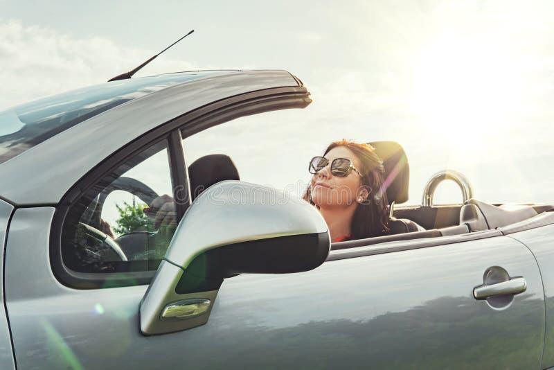 Viagem por estrada do ver?o Viaja a uma atuação com telhado aberto Assento satisfeito da mulher relaxado no carro contra o céu co imagens de stock