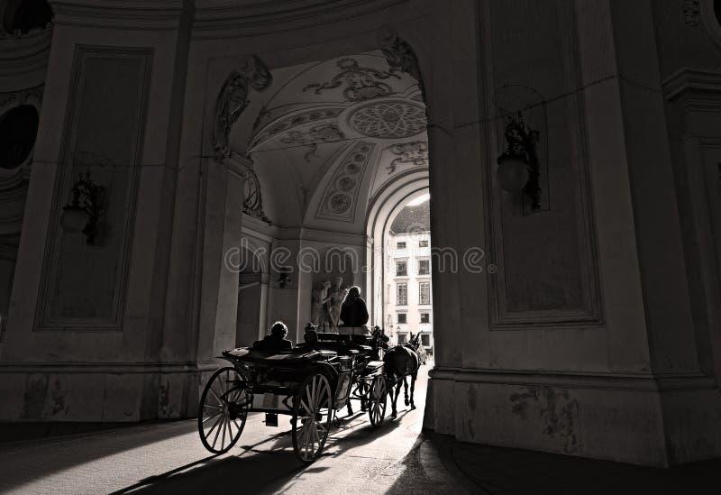 Viagem romântica em um fiacre puxado por cavalos através da porta de Michaelertrakt no centro histórico de Viena, Áustria fotos de stock