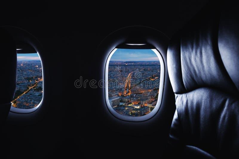 Viaggiando in aeroplano, osservando con la vista piana della città e della finestra la notte fotografia stock
