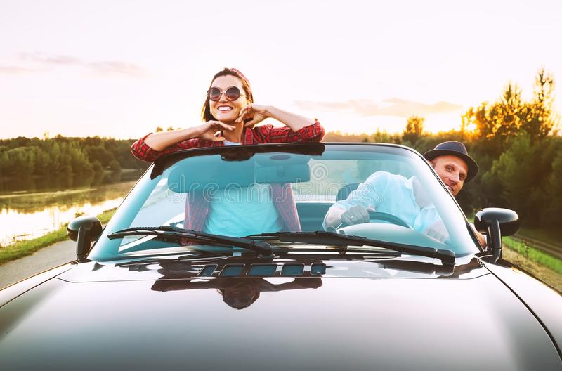 Viaggiando dalle coppie automobilistiche nell'amore va in macchina del cabriolet nel tramonto fotografie stock