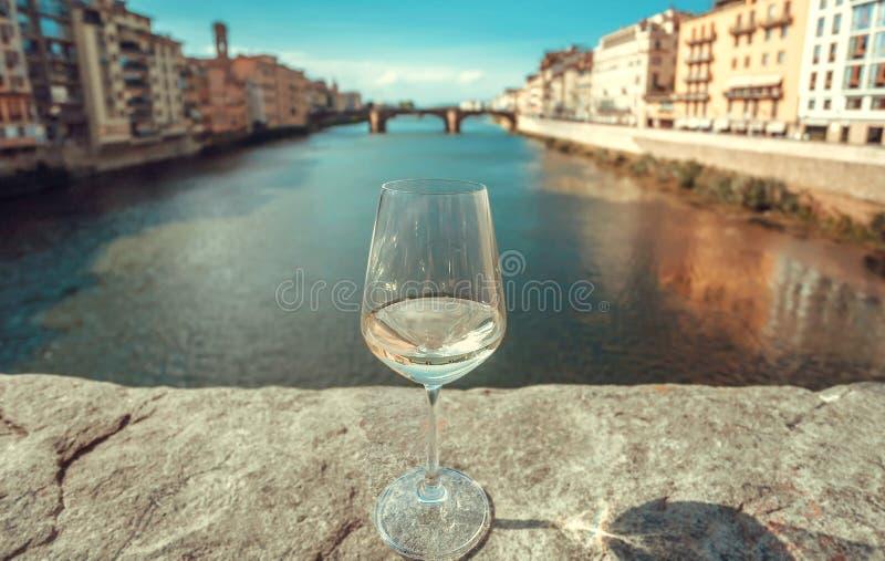 Viaggiando intorno all'Italia con il vetro di vino Vecchie costruzioni di Firenze con il fiume e di paesaggio urbano in Italia fotografie stock libere da diritti