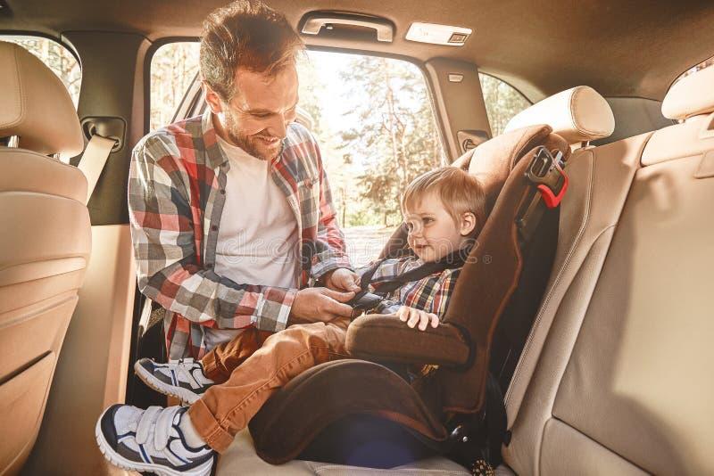 Viaggiando nella società di quelli che amiamo è domestico nel moto Padre che fissa il suo neonato che sedendosi in un'automobile  immagini stock