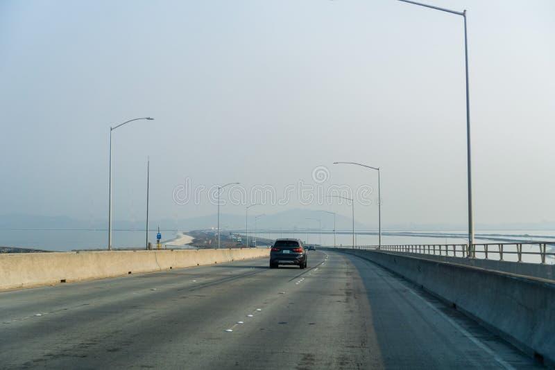 Viaggiando sul ponte di Dumbarton verso area di San Francisco Bay orientale; fumo ed inquinamento nell'aria dagli incendi violent immagine stock libera da diritti