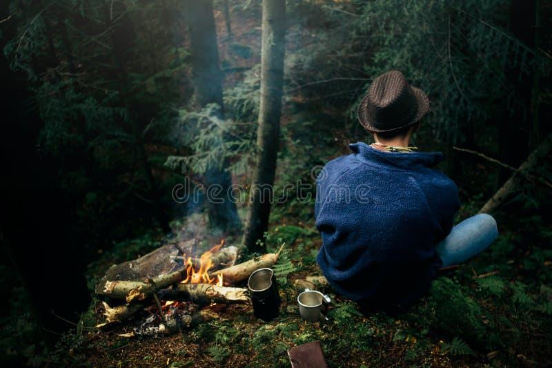 Viaggiatore alla moda dei pantaloni a vita bassa che si accampa nella foresta soleggiata nella montagna fotografia stock