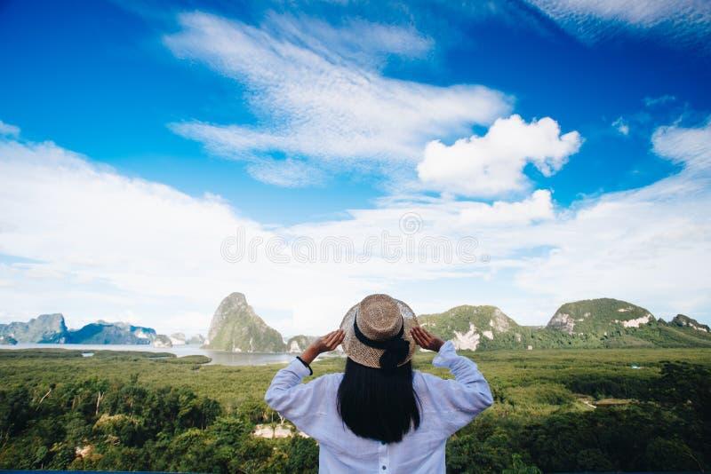 Viaggiatore asiatico della donna che indossa un cappello e un looki bianchi della tenuta della camicia fotografia stock libera da diritti