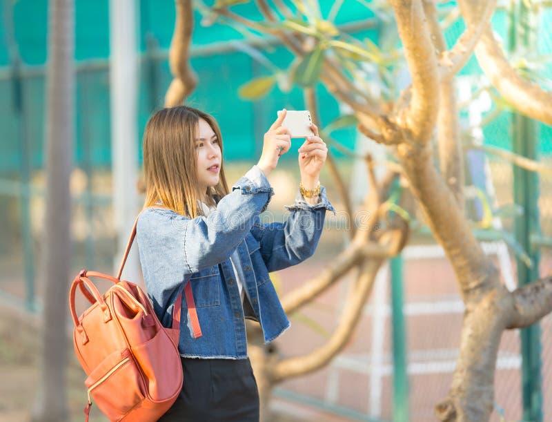 Viaggiatore asiatico della donna che per mezzo del telefono cellulare per la presa della foto fotografia stock libera da diritti