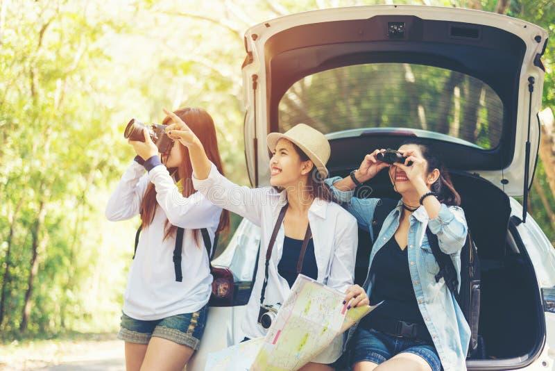 Viaggiatore asiatico della donna del gruppo di viaggio che si siede sull'automobile della berlina per la strada di viaggio con la fotografia stock