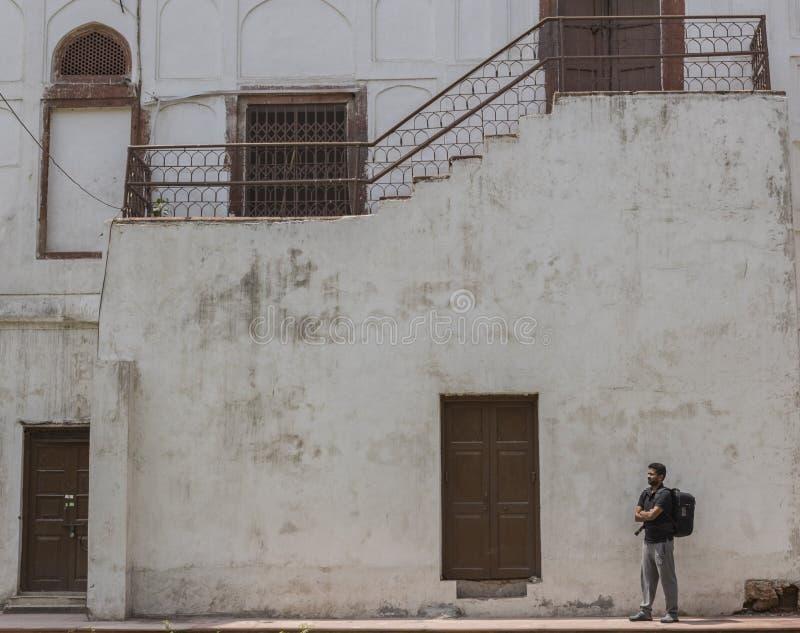 Viaggiatore Backpacking che esamina la bellezza della fortificazione rossa con le pareti bianche e le porte marroni nei precedent fotografia stock libera da diritti