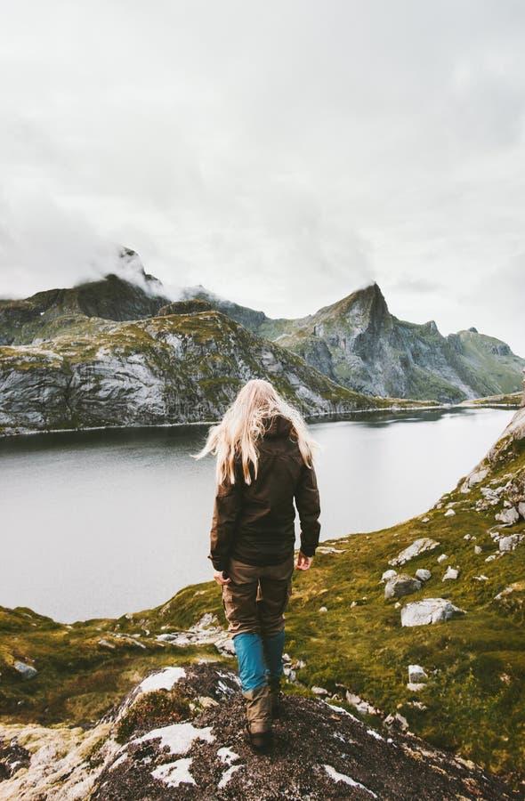 Viaggiatore biondo della donna che cammina da solo alle montagne del lago immagine stock