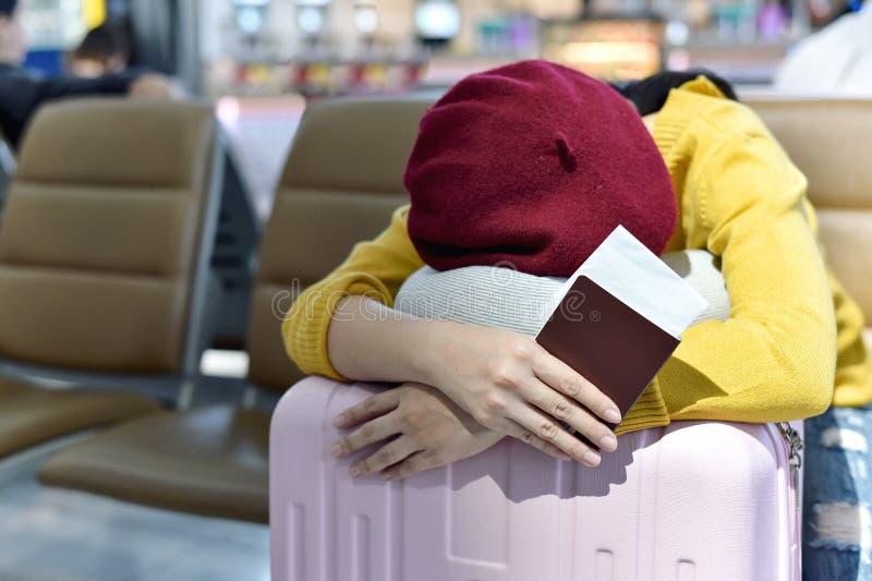 Viaggiatore che aspetta e che dorme al terminale di aeroporto del salotto di area, passeggero stanco per in ritardo imbarcarsi su fotografie stock libere da diritti