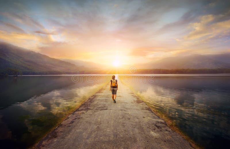 Viaggiatore che cammina lungo la strada alle montagne fotografia stock