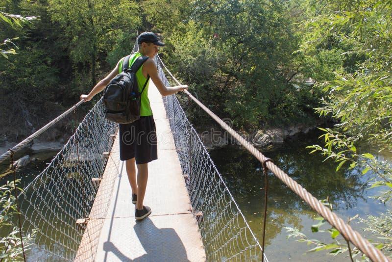 Viaggiatore che guarda la natura dal ponte sospeso Stile di vita attivo e sano durante il giro di fine settimana e di vacanze est fotografia stock