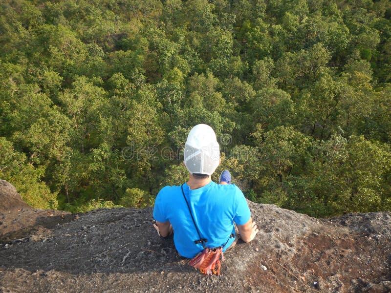 Viaggiatore che si siede al bordo di una scogliera che guarda dall'alto in basso gli alberi verdi fotografie stock