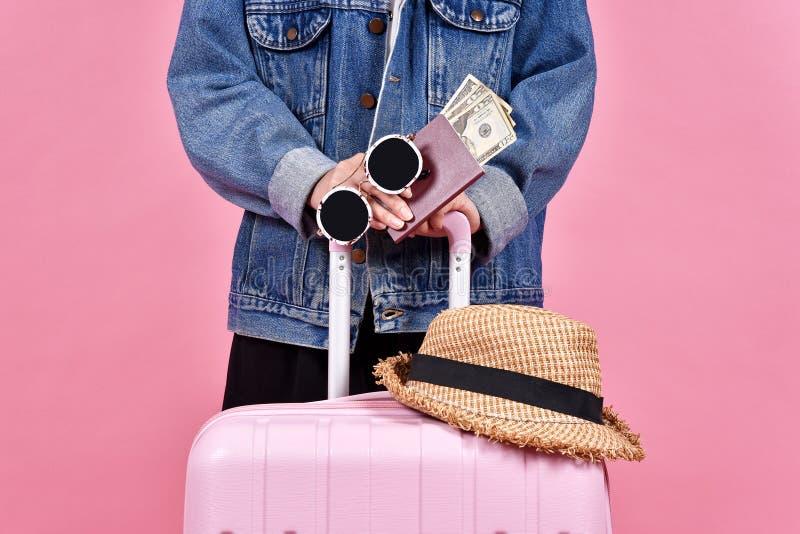 Viaggiatore che tiene valigia rosa, il documento del passaporto e del passeggero sopra fondo rosa fotografia stock
