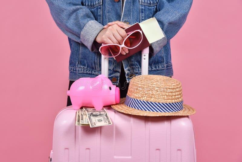 Viaggiatore che tiene valigia rosa, il documento del passaporto e del passeggero sopra fondo rosa immagine stock libera da diritti