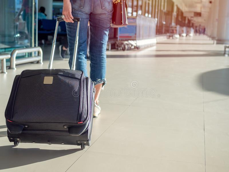 Viaggiatore con la valigia sulla piattaforma in terminale di aeroporto fotografia stock libera da diritti