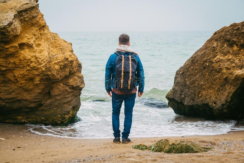 Viaggiatore con una condizione dello zaino vicino ad una roccia contro un bello mare con le onde, un ragazzo alla moda dei pantal immagini stock libere da diritti