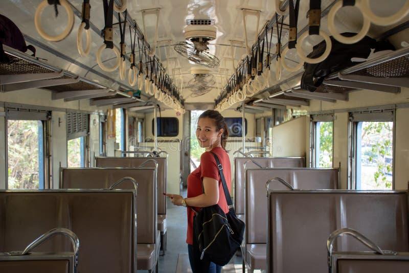 Viaggiatore con zaino e sacco a pelo asiatico dentro il treno pubblico sulla vacanza immagini stock