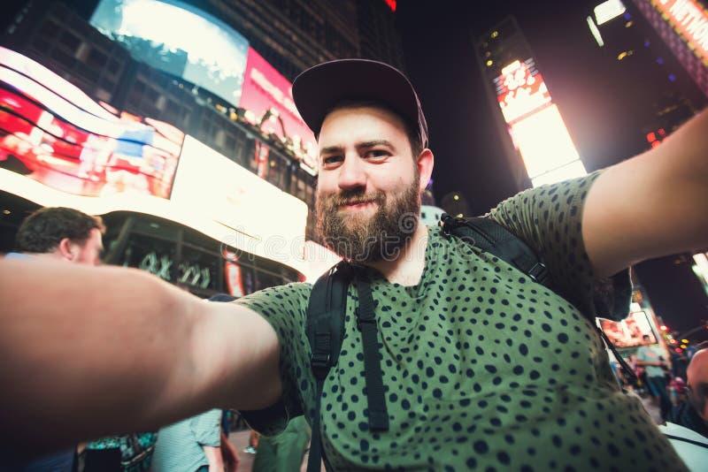 Viaggiatore con zaino e sacco a pelo barbuto divertente dell'uomo che sorride e che prende la foto del selfie sul Times Square a  immagine stock