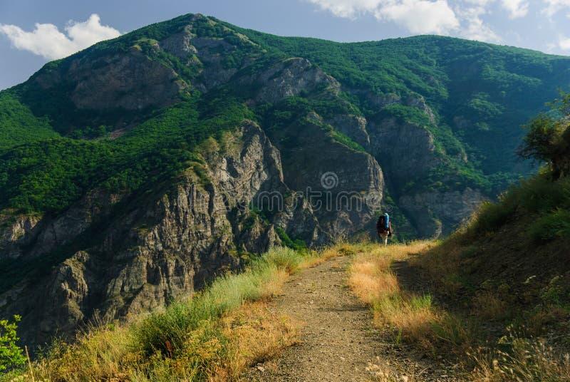 Viaggiatore con zaino e sacco a pelo che fa un'escursione nelle montagne armene maestose di estate, Tatev, Armenia fotografia stock