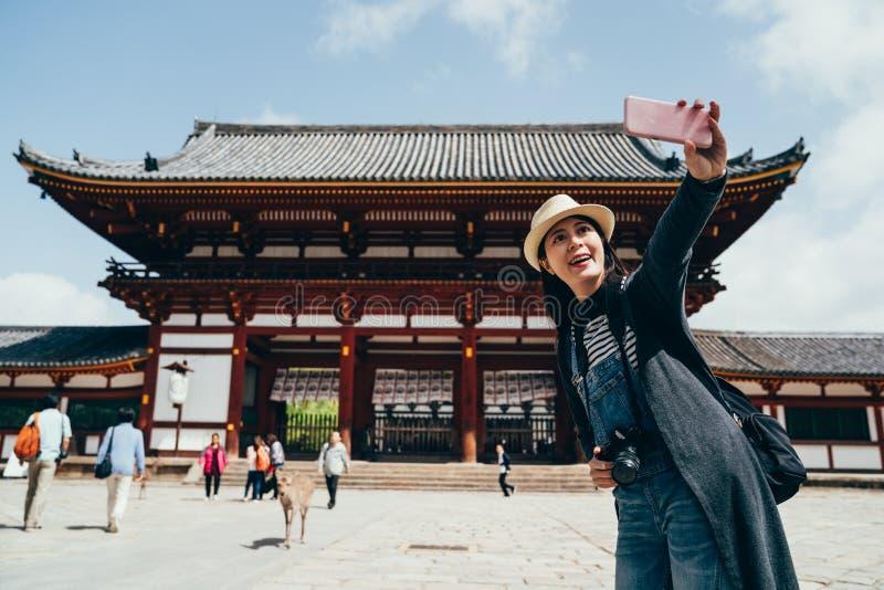 Viaggiatore con zaino e sacco a pelo che rende ad autoritratto tempio giapponese fotografia stock libera da diritti