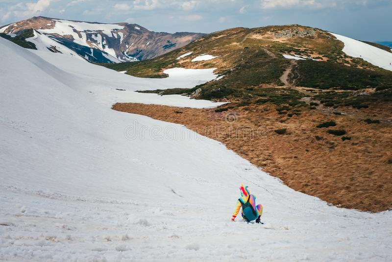 Viaggiatore con zaino e sacco a pelo in costume dell'unicorno divertendosi in montagne nevose fotografia stock libera da diritti