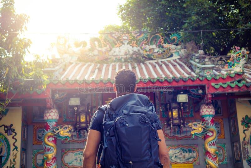 Viaggiatore con zaino e sacco a pelo degli uomini che esamina un tempio a Bangkok durante il giorno, Tailandia, Sud-est asiatico immagine stock