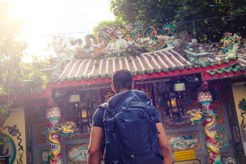 Viaggiatore con zaino e sacco a pelo degli uomini che esamina un tempio a Bangkok durante il giorno, Tailandia, Sud-est asiatico fotografia stock libera da diritti