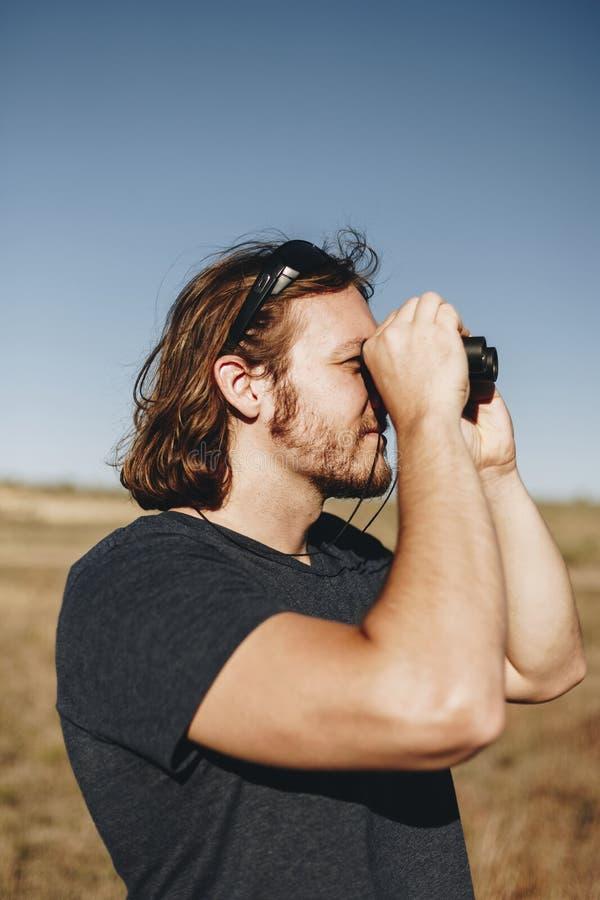 Viaggiatore con zaino e sacco a pelo dell'uomo del viaggiatore facendo uso del binocolo fotografia stock libera da diritti