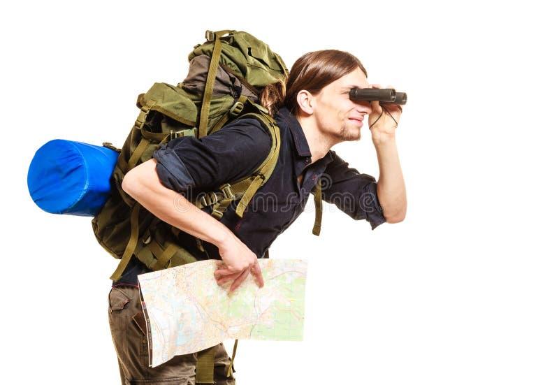 Viaggiatore con zaino e sacco a pelo dell'uomo con la mappa che guarda tramite il binocolo immagine stock libera da diritti