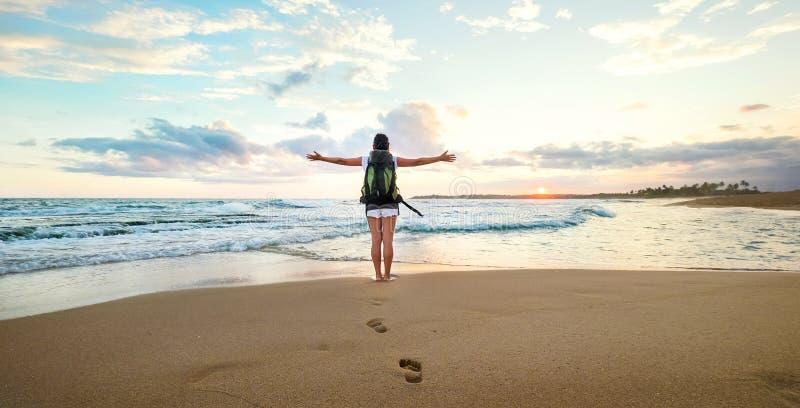 Viaggiatore con zaino e sacco a pelo della donna che accoglie un tramonto alla costa dell'oceano fotografie stock