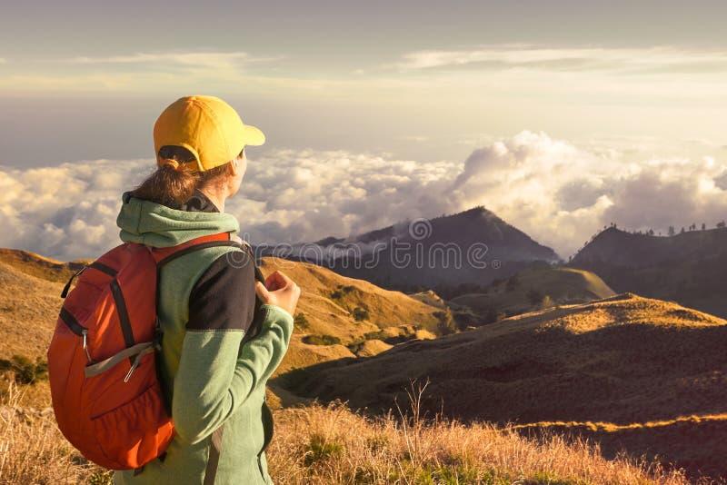 Viaggiatore con zaino e sacco a pelo della donna che viaggia con lo zaino che sta sopra immagine stock