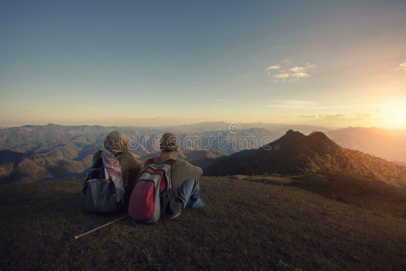 Viaggiatore con zaino e sacco a pelo della donna e dell'uomo che si siede sopra l'alto moutain con la pentola immagini stock libere da diritti