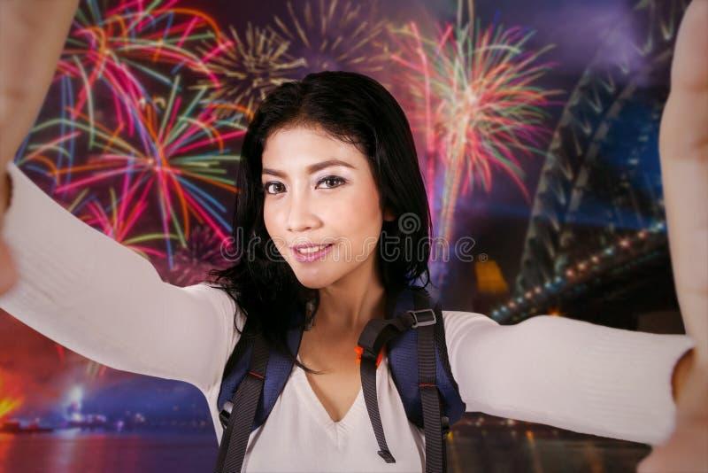 Viaggiatore con zaino e sacco a pelo femminile che prende selfie nel partito dei fuochi d'artificio fotografia stock
