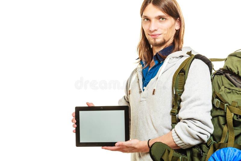 Viaggiatore con zaino e sacco a pelo con la compressa Copyspace dello schermo in bianco immagini stock
