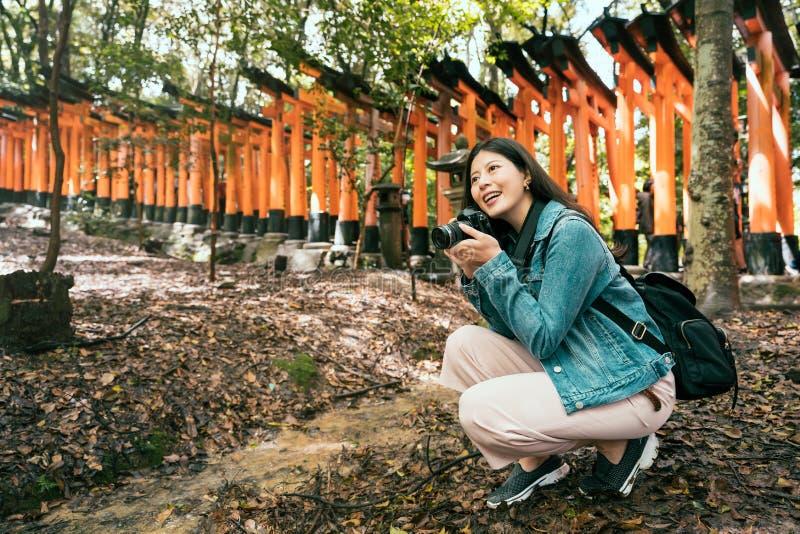 Viaggiatore con zaino e sacco a pelo in tempio che tiene macchina fotografica professionale immagine stock