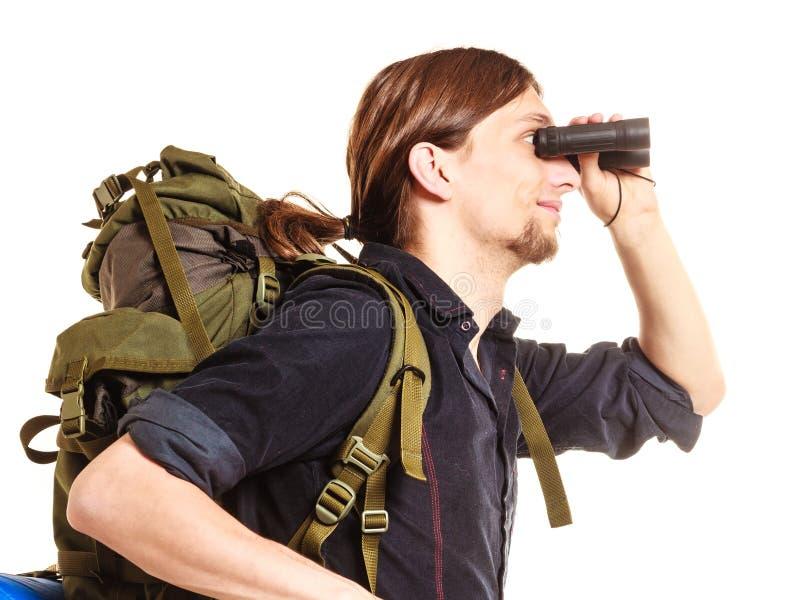 Viaggiatore con zaino e sacco a pelo turistico dell'uomo che guarda tramite il binocolo immagine stock